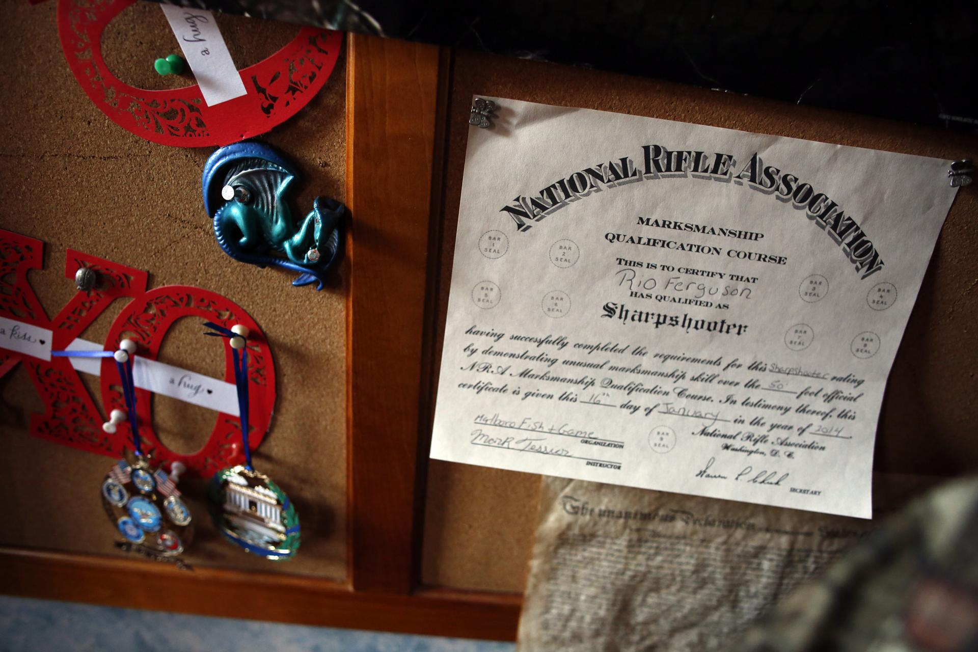 An NRA Marksman Qualification Course certificate hangs on the bulletin board in Rio Ferguson's bedroom.